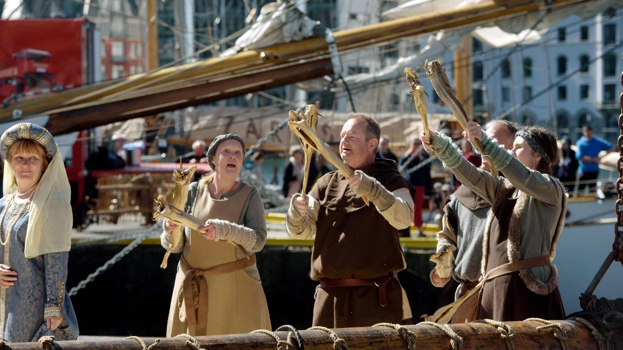 Syngende med tørrfisk i båt